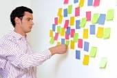 Businessman holding sticky notes — Stock Photo