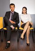 Businessman and businesswoman sitting — Stock Photo