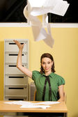 Businesswoman throwing document — Stock fotografie