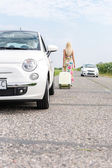Woman leaving broken down car — Stock Photo