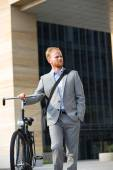Businessman with bicycle looking away — Stock Photo