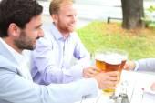Businessmen toasting beer glasses — Stock Photo