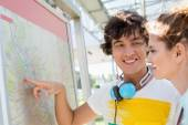 Happy man showing places on map — Stock Photo