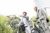 Businessman with bicycle showing something — Stock Photo