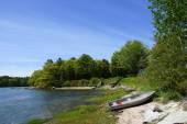 Rocky coastline with metal boat on shore and lined with green tr — Stock Photo