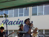 MC Yogi sings into large mike on stage as band jams — Stock Photo