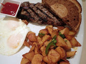 Steak with two eggs over easy, two slices of rye bread, potatos — Stock Photo
