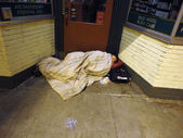 Bundled up homeless person sleep in door way of store under a bl — Stock Photo