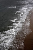 Waves breaking on a sandy beach — Stock Photo
