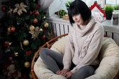 Smiling brunette sitting in the armchair — Stock fotografie
