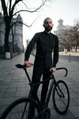 Bearded guy in black clothes stands with fix bike — Stock Photo