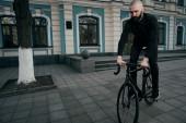 Mann mit Bart in schwarzer Kleidung fährt mit dem Fahrrad ansetzen — Stockfoto