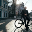 Guy with beard in black clothes sits on fix bike — Stock Photo #71102919