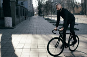 Guy with beard in black clothes rides fix bike — Stock Photo