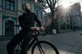 Guy with beard in black clothes sits on fix bike — Stock Photo