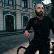 Guy with beard in black clothes sits on fix bike — Stock Photo #72438905