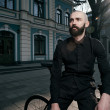 Guy with beard in black clothes sits on fix bike — Stock Photo #72438911
