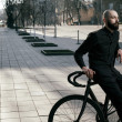 Guy with beard in black clothes sits on fix bike — Stock Photo #72438955
