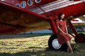 Pin-up lady sitting on airplane wheel in red dress — 图库照片