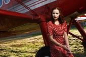 Pin-up lady sitting on airplane wheel in red dress — Stock Photo