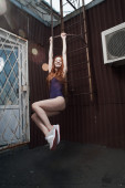 Red haired lady hanging on fire escape in swimsuit — Stock Photo