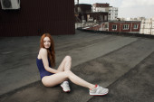 Red haired lady poses on the roof in swimsuit — Stock Photo