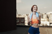 Smiling lady with towel around neck after workout — Stock Photo
