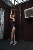 Red haired lady poses near fire escape in swimsuit — Stock Photo