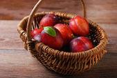 Fresh plums in a wicker basket — Stock Photo