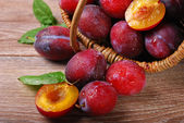 Fresh plums falling out of a basket  — Stock Photo