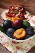 Fresh plums in bowl and fruit cake on plate — Stock Photo