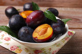 Fresh plums in bowl on wooden background — Stock Photo