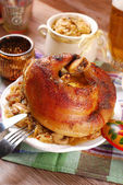 Roasted in beer pork knuckle with sauerkraut for dinner — Stock Photo