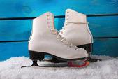 Ice skates on blue wooden background — Stock Photo