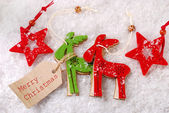 Felt reindeers and stars decorations on snow with paper tag  — Stock Photo
