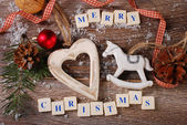 Merry christmas greeting card on wooden background — Stock Photo