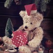 Vintage teddy bear in santa hat holding christmas gift box — Stock Photo #60025903