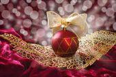 Crimson christmas bauble on openwork golden leaf — Stock Photo