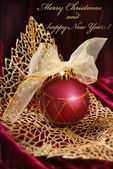 Crimson christmas bauble on golden openwork  leaf — Stock Photo