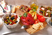 Appetizers and antipasti on wooden table — Stock Photo
