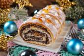 Sliced christmas poppy seed cake with icing and snowflake sprink — Stok fotoğraf