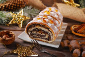 Sliced christmas poppy seed cake with icing and snowflake sprink — Stock Photo