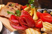 Wooden board with appetizer — Stock Photo