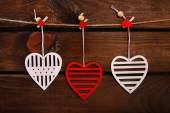 Valentine hearts hanging on wooden background — Stock Photo