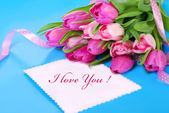Bunch of pink tulips and white card with love text — Stock Photo