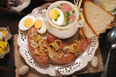 Easter white borscht and sausage on rural wooden table — Stock Photo