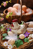 Easter decoration of hen in the nest and wicker basket with eggs — Stock Photo