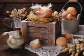 Rustic still life with eggs in nest on wooden box for easter — Stock Photo