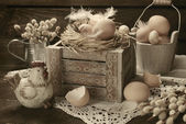 Old rustic still life with eggs in nest on wooden box for easter — Stock Photo