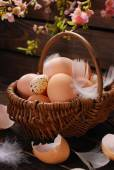 Easter eggs in wicker basket on wooden background — Stock Photo